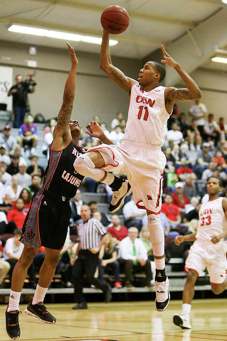 UIW's Denzel Livingston drives to the basket on Louisiana-Lafayette's Jay Wright during the first half of their first round game with Louisiana-Lafayette in the CollegeInsider.com Tournament at the McDermott Convocation Center on March 17, 2015. Photo: Marvin Pfeiffer /San Antonio Express-News / Express-News 2015