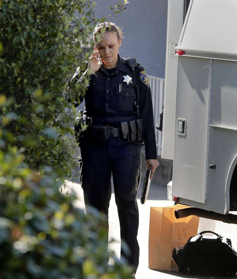 A Napa police officer spoke on the phone by the crime scene truck in the driveway where the body was discovered on Brown Street. A body in a freezer was discovered near downtown Napa, Calif. Tuesday March 17, 2015. Photo: Brant Ward, The Chronicle