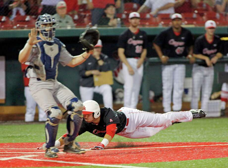 Justin Montemayor comes flying home on a double by Connor Wong for the first tally in UH's five-run fourth inning Tuesday night. Photo: Craig Hartley, Freelance / Copyright: Craig H. Hartley