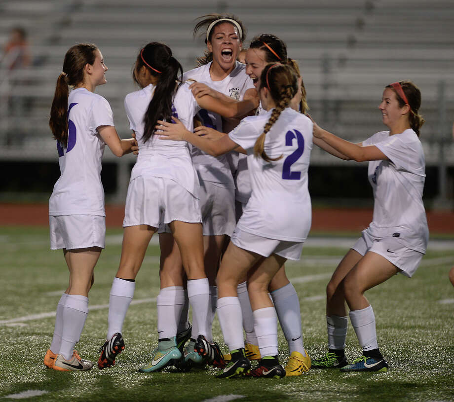 Port Neches - Groves' Mikayla Johnson (center) is swarmed by teammates as they celebrate her opening goal against Vidor during their district match-up Tuesday at The Reservation.  Photo taken Tuesday, March 17, 2015  Kim Brent/The Enterprise Photo: Kim Brent / Beaumont Enterprise