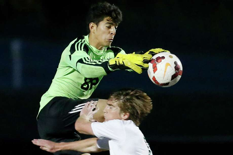 Lee goalkeeper Victor Rodriguez makes a stop at a shot at the goal against Reagan's Edgar Guajardo (17) during their soccer game at Comalander Stadium on March 17, 2015. Photo: Kin Man Hui /San Antonio Express-News / ©2015 San Antonio Express-News