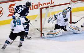Winnipeg Jets' Blake Wheeler (26) knocks a puck out of the air to beat San Jose Sharks' goaltender Alex Stalock (32) during third period NHL hockey action in Winnipeg, Manitoba, Tuesday, March 17, 2015. (AP Photo/The Canadian Press, Trevor Hagan)