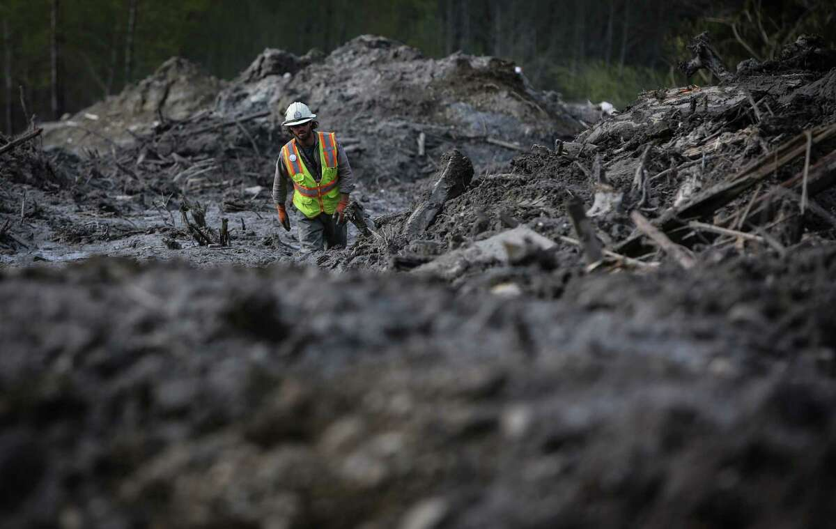 Oso landslide -- 2014 Ben Woodward slogs through thick mud at the scene of the Oso mudslide.