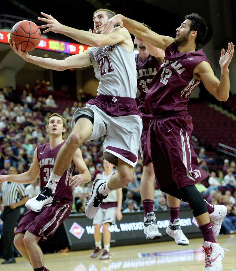 Texas A&M's Alex Caruso (21) drives the lane against Montana's Martin Breunig (12) and Michael Weisner (33) in the first half of an NIT Tournament first-round NCAA basketball game Tuesday, March 17, 2015, in College Station, Texas. Photo: Sam Craft, AP / AP
