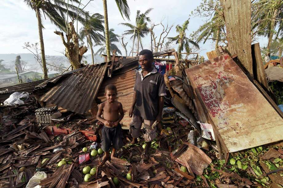 "Samuel, only his first name given, and as his father, Phillip, right, stand amongst of their destroyed home in Port Vila, Vanuatu in the aftermath of Cyclone Pam Monday, March 16, 2015. Vanuatu's President Baldwin Lonsdale said Monday that the cyclone that hammered the tiny South Pacific archipelago over the weekend was a ""monster"" that has destroyed or damaged 90 percent of the buildings in the capital and has forced the nation to start anew. (AP Photo/Dave Hunt, Pool) Photo: Dave Hunt, AP Images / AAP Pool"