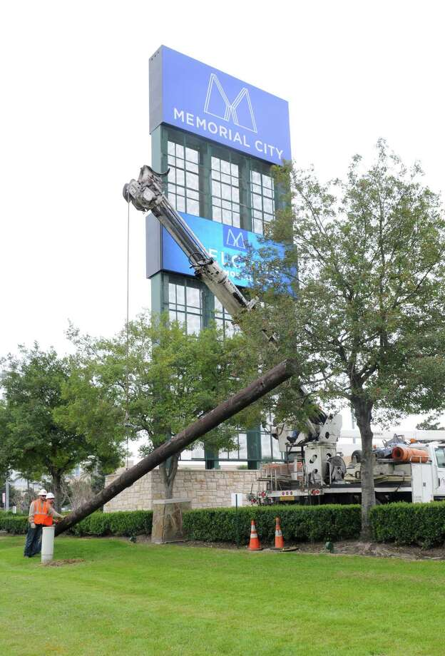 MPT workers laying down the final remaining 45ft. power pole in front of Memorial City Mall. Photo: George Wong / Freelance