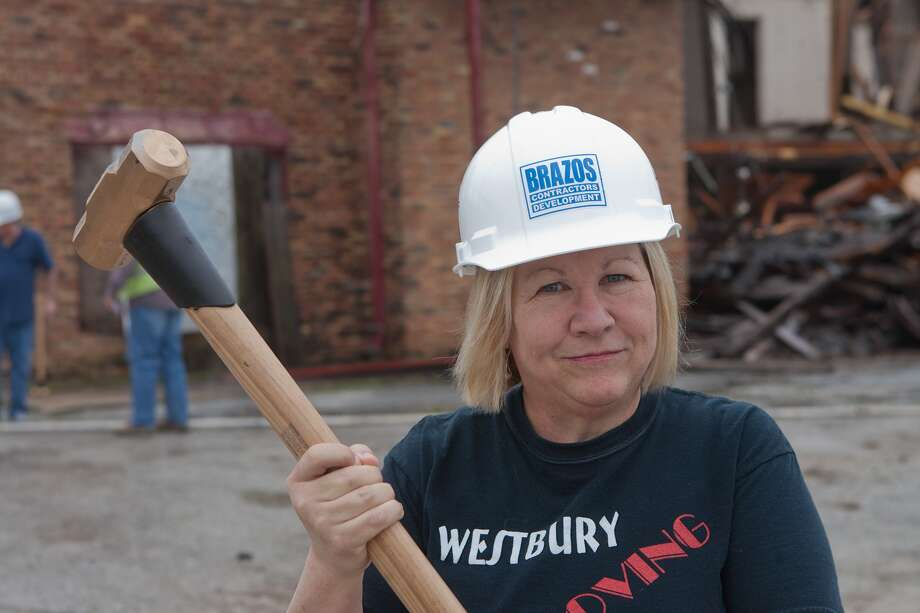 "Westbury Civic Club President Becky Edmondson poses with a gold-painted sledgehammer before taking  a few ritual whacks at a Westbury shopping center being demolished. Demolition began on the old ""Westbury Centerette"" shopping/strip center at Chimney Rock and West Bellfort on March 16.  The center, which was built sometime in the late 1950s, has been largely derelict for several years and completely untenanted for nearly a decade.  The site will be redeveloped as an LA Fitness gym. Photo: R. Clayton McKee, Freelance / © R. Clayton McKee"