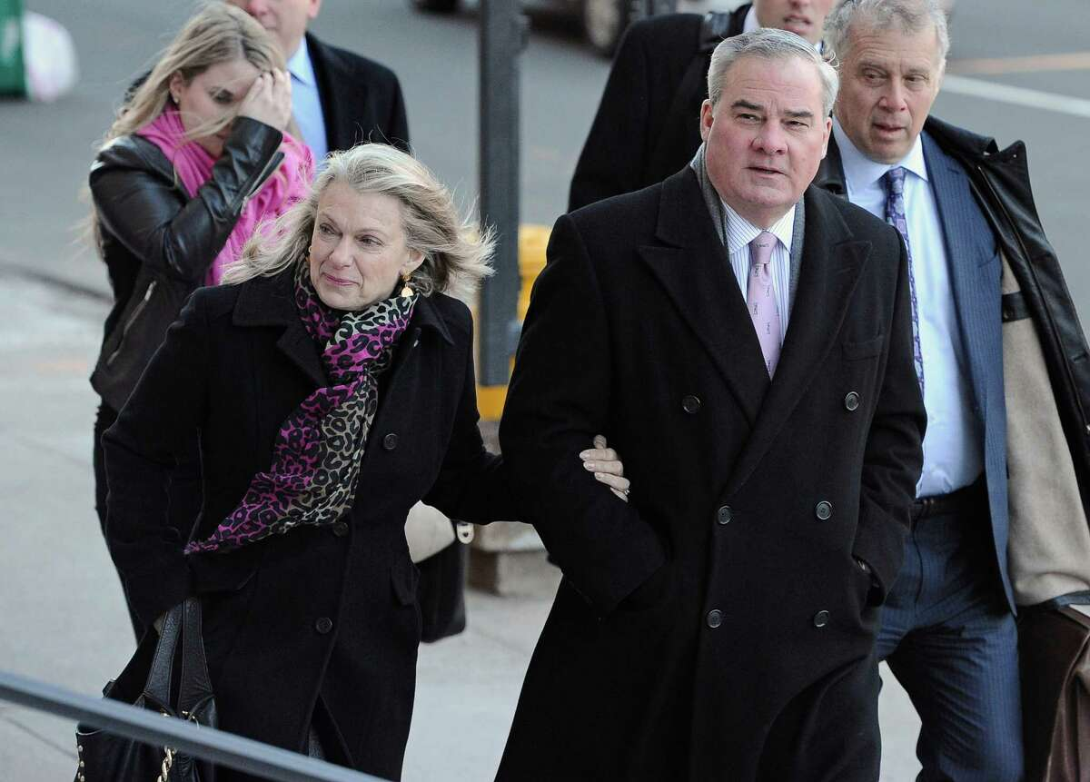 Former Connecticut Gov. John Rowland arrives with his wife Patty Rowland, left, at federal court in New Haven, Wednesday, March 18, 2015, in New Haven, Conn. A federal court jury in New Haven convicted Rowland in September of federal charges that he conspired to hide payment for work on two congressional campaigns. His sentencing on Wednesday will come 10 years to the day that he was sentenced to a year and a day in prison for accepting illegal gifts while in office, including trips and improvements to his lakeside cottage.