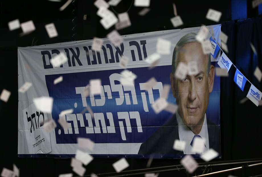 Confetti falls in front of a poster of Israeli Prime Minister Benjamin Netanyahu as supporters of his Likud party celebrate while they wait for the first official results of Israel's parliamentary elections March 17. Photo: Jack Guez, AFP / Getty Images