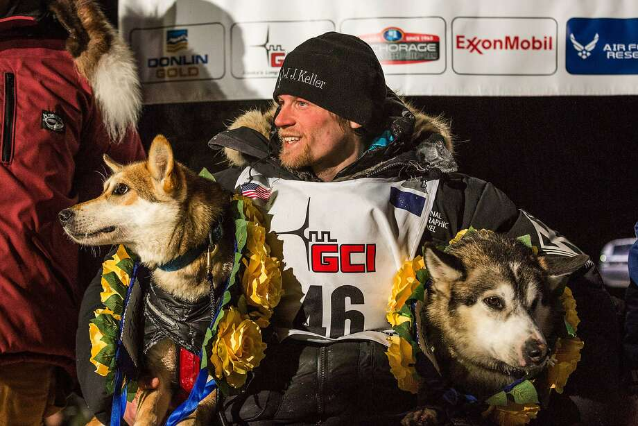 Dallas Seavey poses with his lead dogs Reef, left, and Hero in Nome, Alaska on Wednesday, March 18, 2015 during the Iditarod Trail Sled Dog Race.  Seavey won his third Iditarod in the last four years, beating his father, Mitch, to the finish line after racing 1,000 miles across Alaska. (AP Photo/Alaska Dispatch News, Loren Holmes ) Photo: Loren Holmes, Associated Press