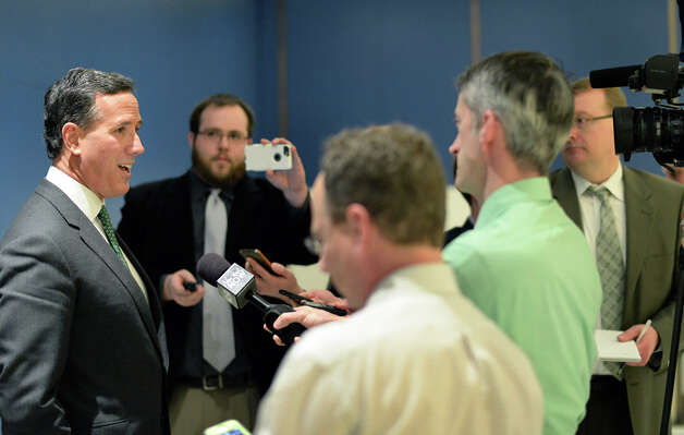 Former presidential candidate Rick Santorum, left, speaks with reporters after addressing the New York Family Research Foundation's lobby day in the Convention Center at the Empire State Plaza Tuesday March 17, 2015 in Albany, NY.  (John Carl D'Annibale / Times Union) Photo: John Carl D'Annibale, Albany Times Union / 00031052A