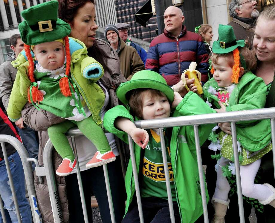 Auston O'Grady, 3, center, and his sisters Billie O'Grady, 7 months, right, and Zola O'Grady, 2, watch the St. Patrick's Day Parade in New York, Tuesday, March 17, 2015. (AP Photo/Seth Wenig) ORG XMIT: NYSW110 Photo: Seth Wenig, AP / AP