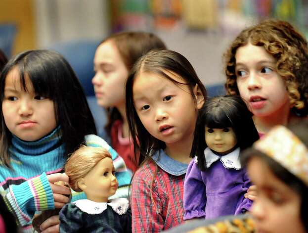 Sisters, from left, LeeAna, 9, Maggie, 7, and Kelley Doolin, 10, of Guilderland bring their American Girl dolls to Hina Matsuri, the Japanese Doll Festival, on Saturday, March 28, 2009, at the Guilderland Public Library in Guilderland, N.Y. The girls learned about the Japanese day dedicated to dolls and girls, made a paper doll and had a snack. (Cindy Schultz / Times Union) Photo: CINDY SCHULTZ / 00003029A