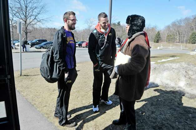 University at Albany basketball players, Sam Rowley, left, and Peter Hooley, center, talk with UAlbany professor Leonard A. Slade, Jr. before getting on a bus at the college on Wednesday, March 18, 2015, in Albany, N.Y.  The team was heading to the airport to fly to Columbus for the NCAA Tournament.  (Paul Buckowski / Times Union) Photo: PAUL BUCKOWSKI / 00031071A