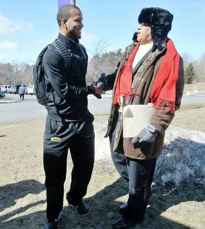 University at Albany basketball player Ray Sanders, left, talks with UAlbany professor Leonard A. Slade, Jr. before getting on a bus on Wednesday, March 18, 2015, in Albany, N.Y.  Slade came over to see the players off.   The team was heading to the airport to fly to Columbus for the NCAA Tournament.  (Paul Buckowski / Times Union) Photo: PAUL BUCKOWSKI / 00031071A