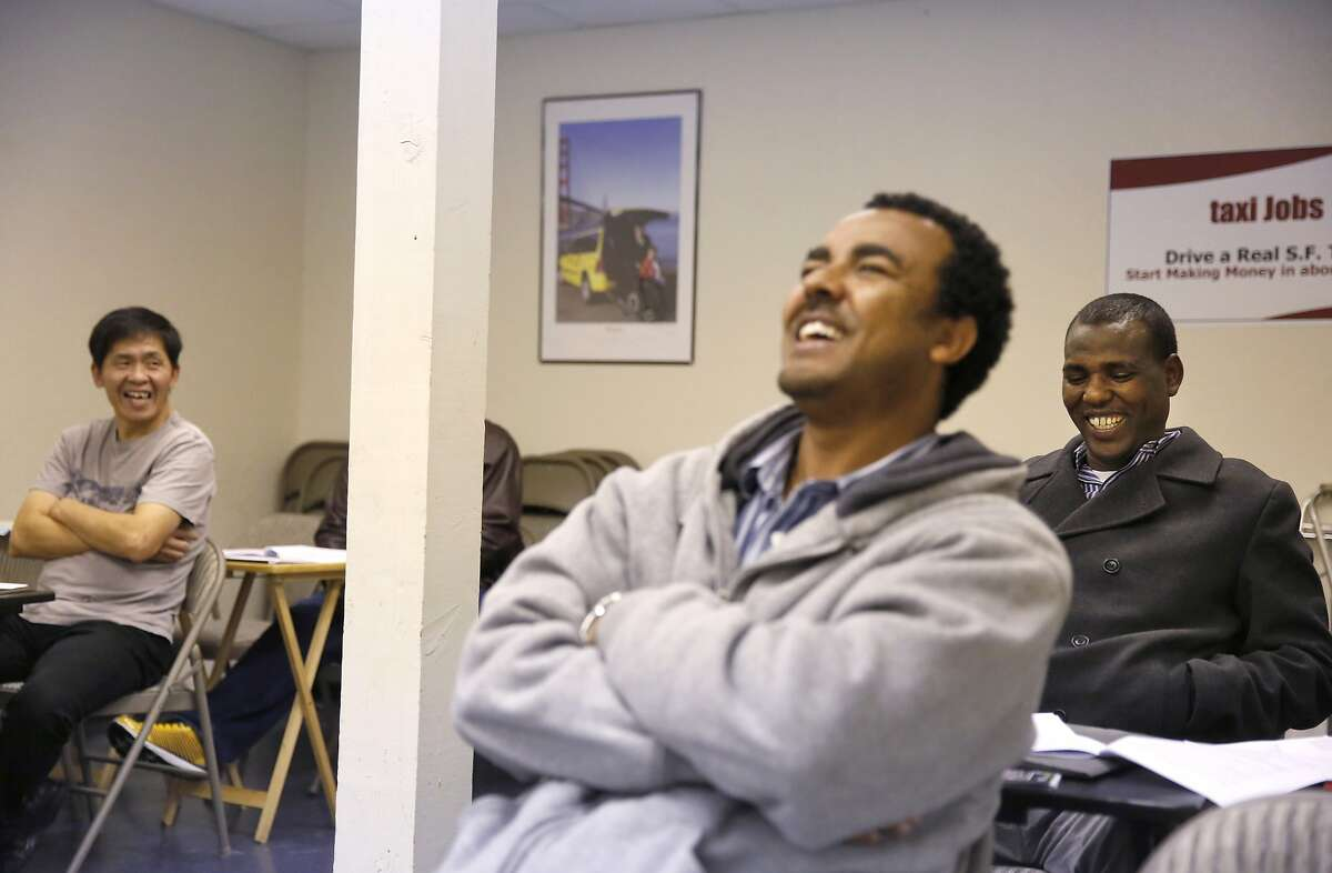 Students, from left, Dashzeveg Erdenebileg, Yikuno Tesfay, and Mesele Teclehaimanot laugh after the instructor Mickey Kelley made a joke during class at San Francisco Taxi School at the DeSoto Cab and Flywheel headquarters March 18, 2015 in San Francisco, Calif.