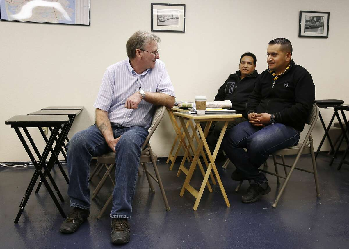 Instructor Mickey Kelley, left, plays a cab driver in a mock situation with Ali Abdulazeez, right, as fellow student Doni Ramirez, center, listens during class at San Francisco Taxi School at the DeSoto Cab and Flywheel headquarters March 18, 2015 in San Francisco, Calif.