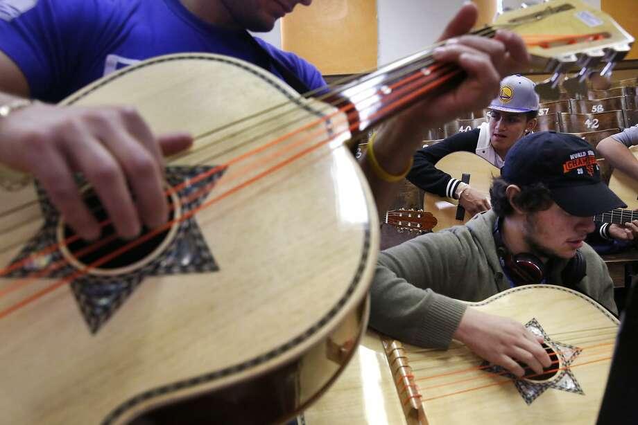 Instructor Hector Aguilar (left), Ed Almengor, 17, and Oscar Biliz, 19, at Mission High's mariachi class. Photo: Leah Millis, The Chronicle