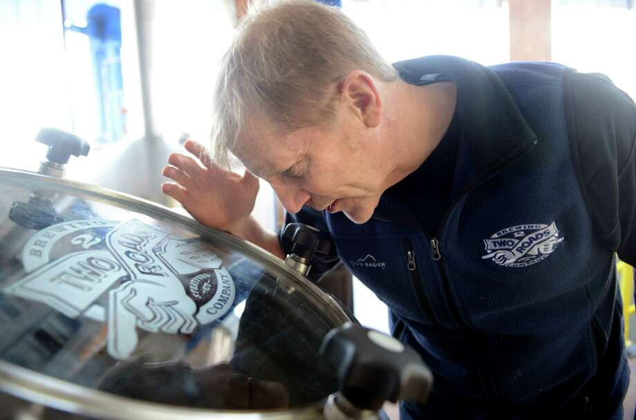 Two Roads Brewing Company executive Brad Hittle peers into a beer vessel at the company's brewery in Stratford, Conn., Wednesday, Mar. 18, 2015. Photo: Autumn Driscoll / Connecticut Post