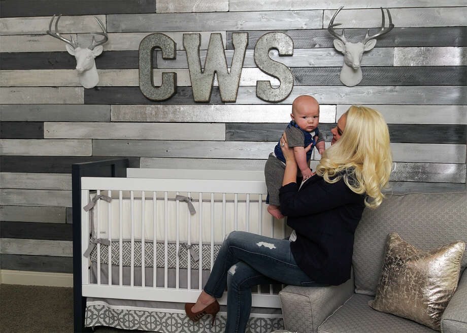 Brittany Ivey, with 6-month-old son Cash, sits in his nursery. Ivey enlisted San Antonio nursery designer Katy Mimari, owner of Caden Lane, to accomplish the sleek, modern aesthetic that will easily transition as the baby grows out of his crib. Photo: Alma E. Hernandez / For The Express-News