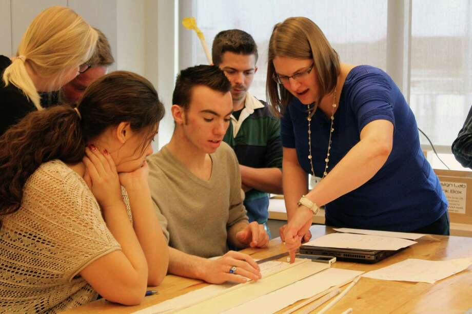 EYP Architecture and Engineering Architect Courtney Laflin works with TVHS seniors Andrew Glanton and Alyssa Decker on their bridge design at an event between Tech Valley High School students and architects from EYP Architecture.Students worked alongside the architects to build scale models of local bridges the students redesigned during their pre-calculus course. The engineers provided hands-on expertise on how to construct scale models in architecture. EYP Architecture also used the opportunity to announce its continued financial support of the EYP Fab Lab, a space students use for hands-on construction projects. (Submitted photo)