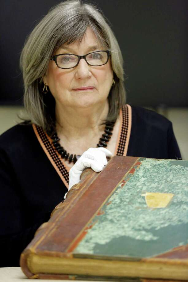 Karen Glenney, University Health System's archivist, holds the oldest bound volumes of the San Antonio City Hospital's patient registry on Feb. 5. The registry starts in 1916. Photo: William Luther /San Antonio Express-News / © 2015 San Antonio Express-News