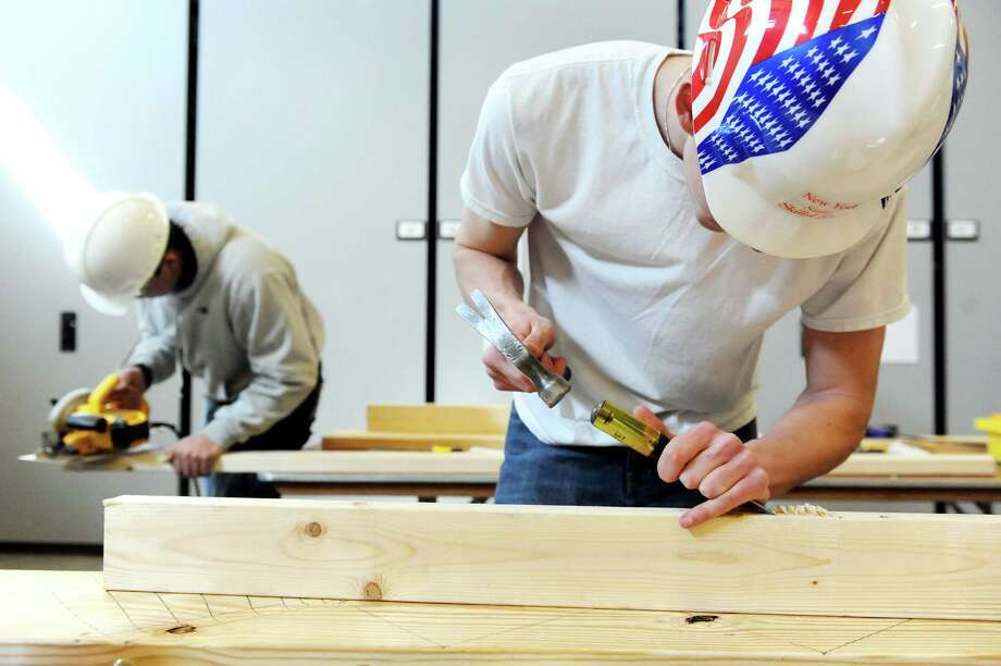Zachary Haskin, 18, of Schoharie County BOCES, right, mortises a hinge during the annual SkillsUSA competition on Wednesday, March 18, 2015, at Stratton Air National Guard Base in Scotia, N.Y. High school students tested their skills including heavy equipment operation, heating equipment repair and nursing. (Cindy Schultz / Times Union) Photo: Cindy Schultz / 00031074A
