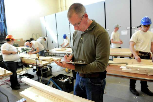 Steve Fairbanks of Curtis Lumber, center, judges the students carpentry skills during the annual SkillsUSA competition on Wednesday, March 18, 2015, at Stratton Air National Guard Base in Scotia, N.Y. BOCES high school students tested their skills including heavy equipment operation, heating equipment repair and nursing. (Cindy Schultz / Times Union) Photo: Cindy Schultz / 00031074A