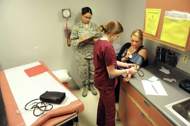 Madi Jones, 16, of Southern Adirondack Educational Center, center, is tested for nursing skills as she takes the blood pressure of Ashley McCarthy, 18, right, during the annual SkillsUSA competition on Wednesday, March 18, 2015, at Stratton Air National Guard Base in Scotia, N.Y. Airman Amy Story judges the procedure. BOCES high school students tested their skills including heavy equipment operation, heating equipment repair and carpentry. (Cindy Schultz / Times Union) Photo: Cindy Schultz / 00031074A