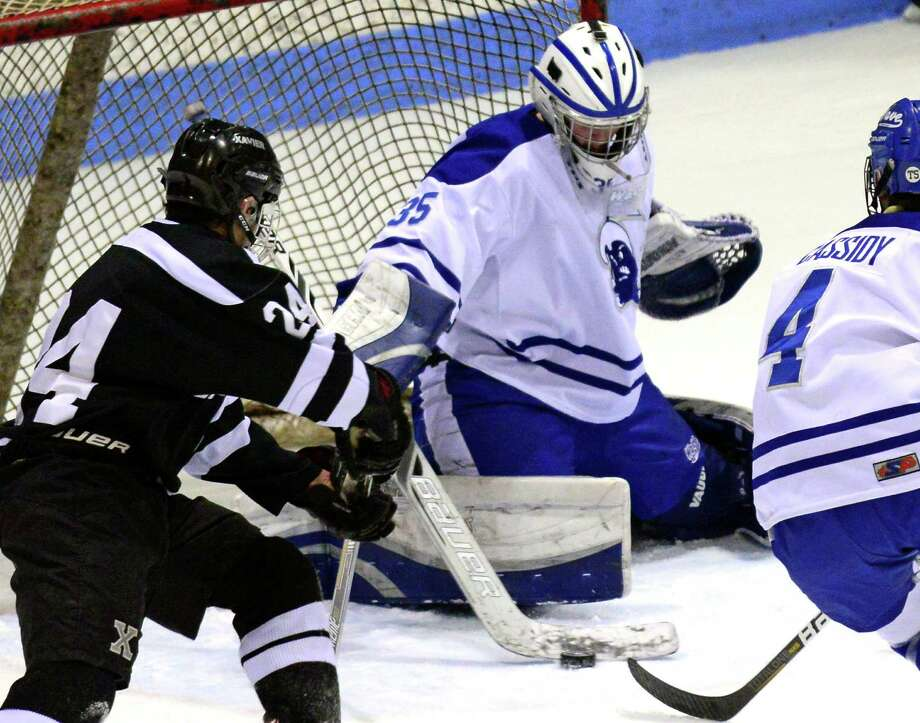 Darien goalie Will Massie deflects the puck, during CIAC State Boys Ice Hockey Tournament action against Xavier in New Haven, Conn., on Wednesday Mar. 18, 2015. At left is Xavier's Alexander Stasiuk. Photo: Christian Abraham / Connecticut Post