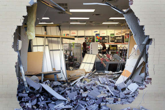 Employees clean up a RadioShack after a smash-and-grab last August in the 5800 block of Lyons Avenue.