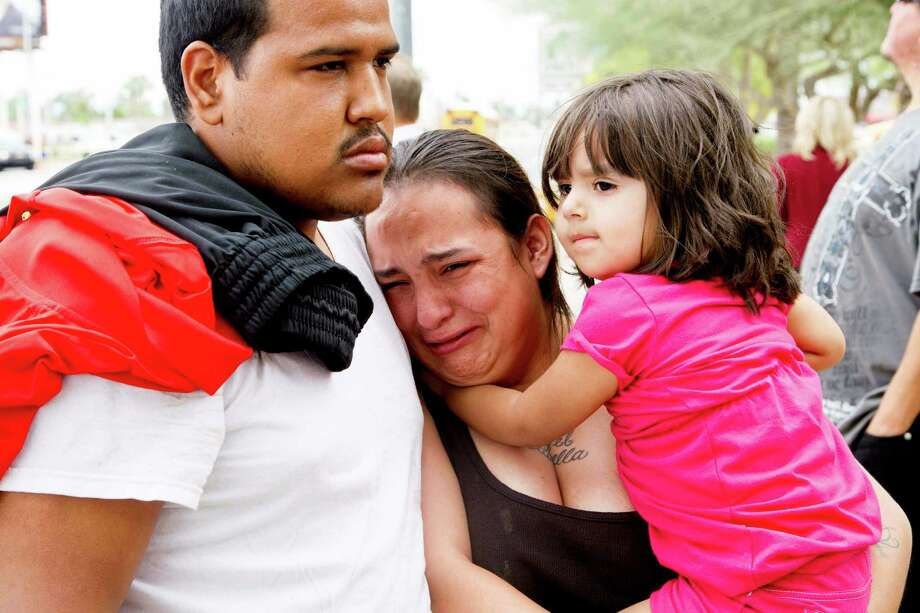 Tanya Ehrig, 27, cries for victims of a shooting as she holds her child Trinity in Mesa, Ariz., on Wednesday, March 18, 2015. A gunman wounded at least four people across multiple locations in the Phoenix suburb and police warned residents to stay indoors as they hunt for the suspect. (AP Photo/The Arizona Republic, Nick Oza) Photo: Nick Oza, MBO / Associated Press / The Arizona Republic
