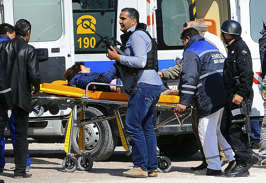 A victim is being evacuated by rescue workers outside the Bardo musum in Tunis, Wednesday, March 18, 2015 in Tunis, Tunisia. Gunmen opened fire at a leading museum in Tunisia's capital, killing at least eight people and wounding six, including foreign tourists, authorities said. A later raid by security forces left two gunmen and one security officer dead but ended the standoff, Tunisian authorities said. (AP Photo/Hassene Dridi) ORG XMIT: XTUN201 Photo: Hassene Dridi / AP