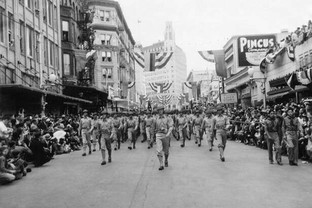 Marchers head down the street in the Battle of Flowers parade in 1941, the year when the Cavaliers decided to introduce the king in a river parade.