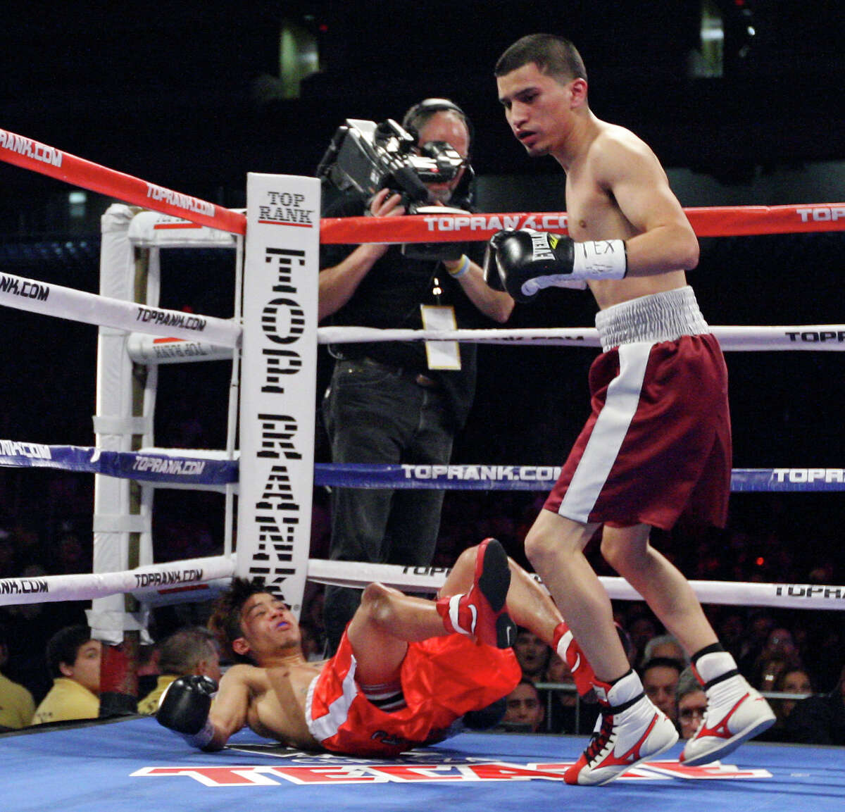 FOR SPORTS - Richard Hernandez (left) falls to the mat after being hit by Adam Lopez during the first round of their bantamweight fight Saturday Feb. 4, 2012 at the Alamodome. Lopez won by TKO in the first round. (PHOTO BY EDWARD A. ORNELAS/SAN ANTONIO EXPRESS-NEWS)