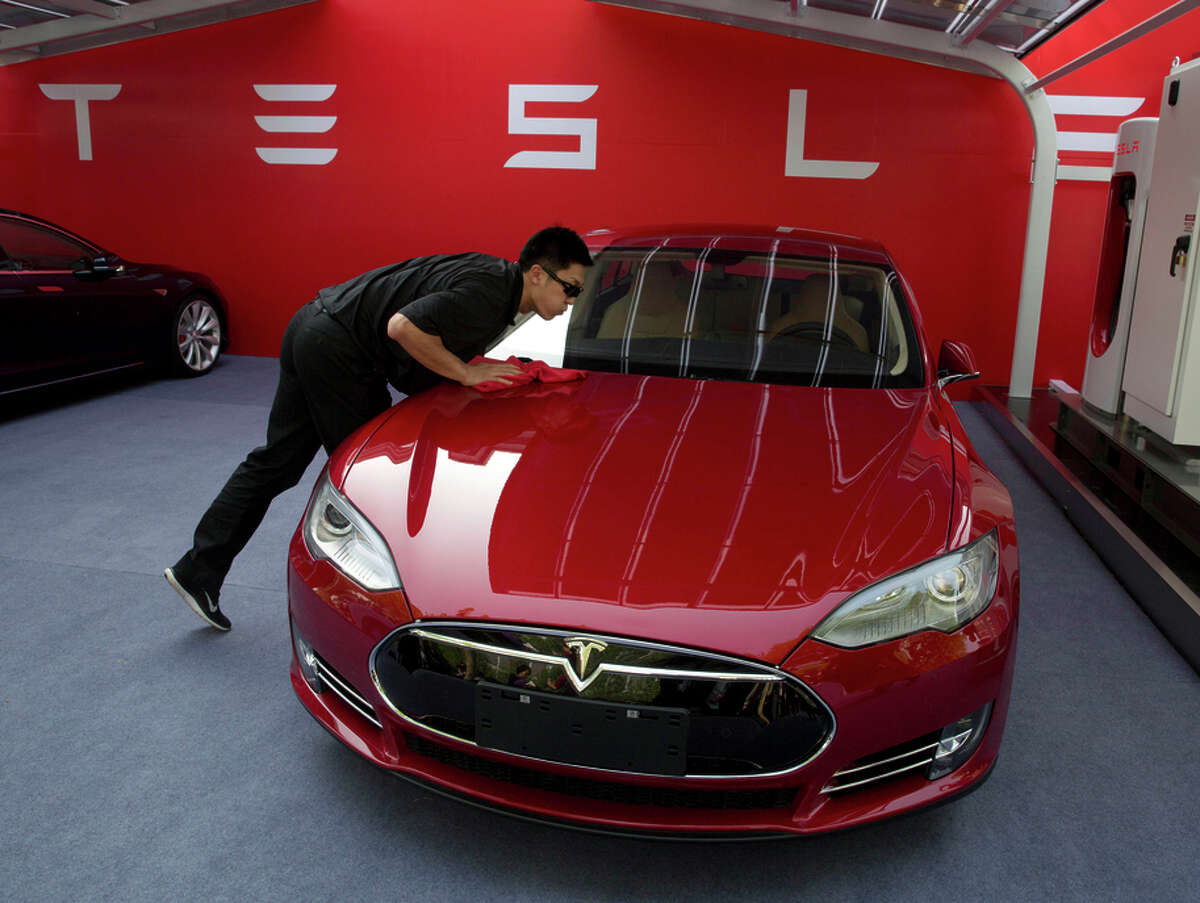 A worker cleans a Tesla Model S sedan before an event to deliver the first of the cars to customers in Beijing last year.