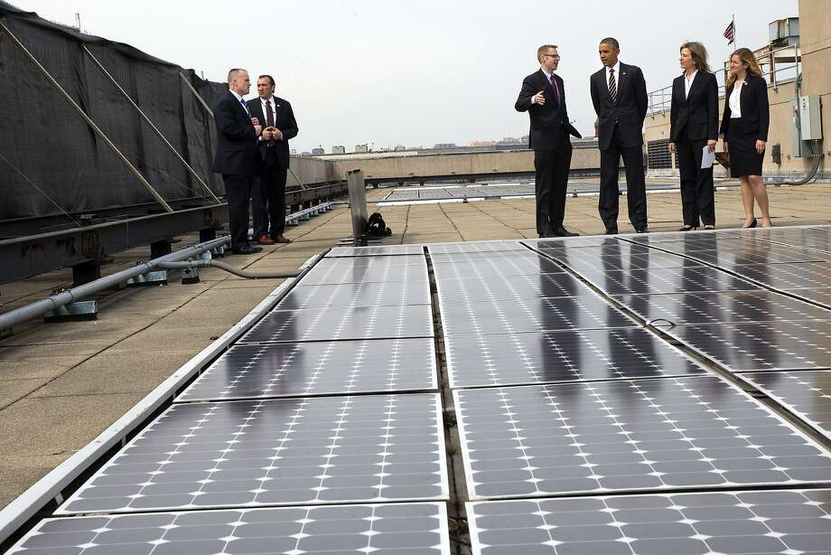 President Obama discusses the solar panels on the roof of the Energy Department with agency officials. Photo: Jacquelyn Martin, Associated Press