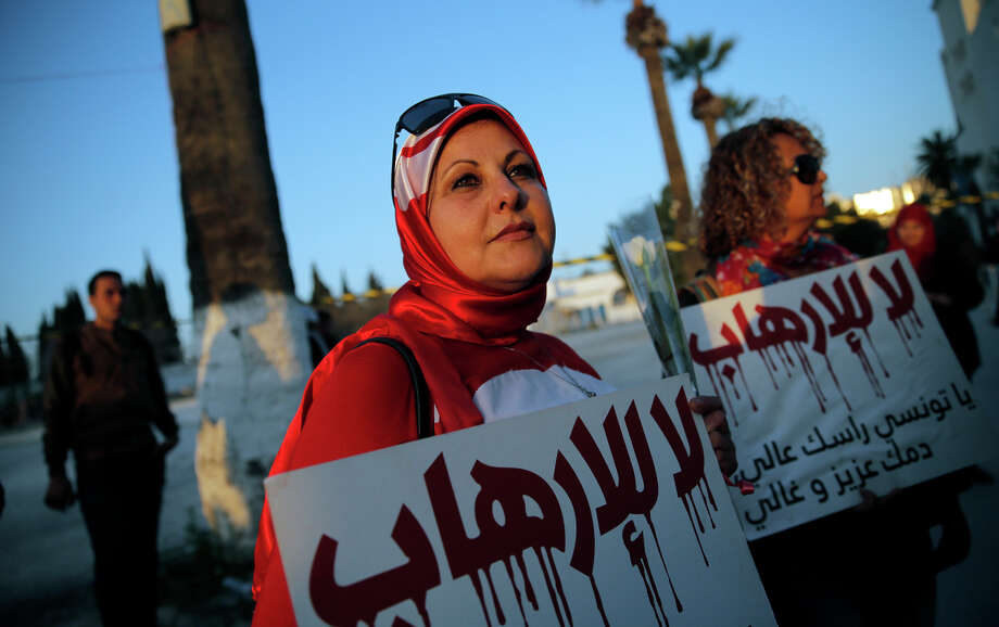 """A Tunisian woman holds a placard reading: """"No to Terrorism"""" a day after an attack on the Bardo museum killed scores of people, including 20 tourists. Photo: Christophe Ena / Associated Press / AP"""