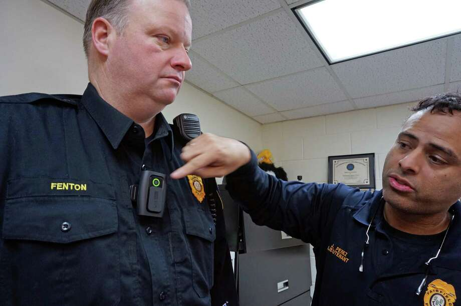 Police Lt. James Perez, right, points out the green circle that indicates a body camera worn by Officer Sean Fenton is recording. Photo: Genevieve Reilly / Fairfield Citizen