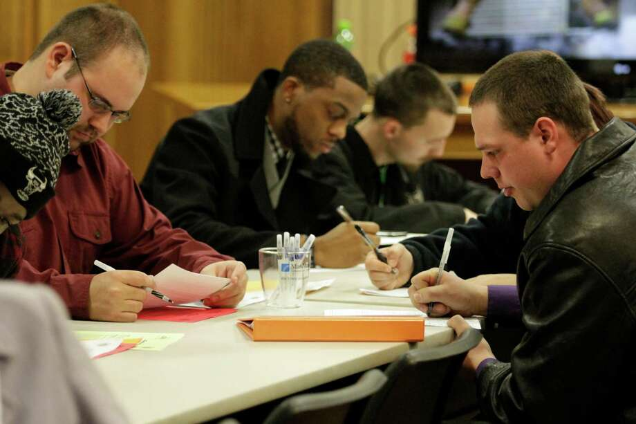 Men fill out applications during a public safety job fair at City Hall in Saginaw, Mich., on Jan. 29. As of February, 5.2 percent of men in the United States were not employed. Photo: David C Bristow / Associated Press / The Saginaw News