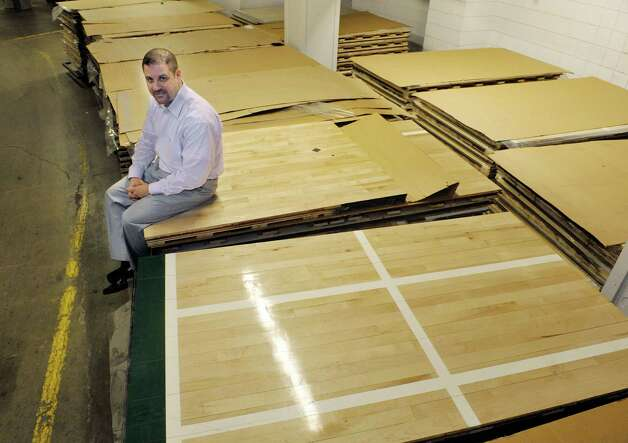 Doug McClaine, assistant general manager and director of operations for the Times Union Center, poses with the basketball floor panels that are stacked up inside the center on Monday, March 16, 2015. The floor which was used in last years NCAA tournament, was purchased this year for use in the TU Center. The floor is 270 pieces and when installed it is 60 feet wide by 120 feet long.   (Paul Buckowski / Times Union) Photo: PAUL BUCKOWSKI / 00031005A
