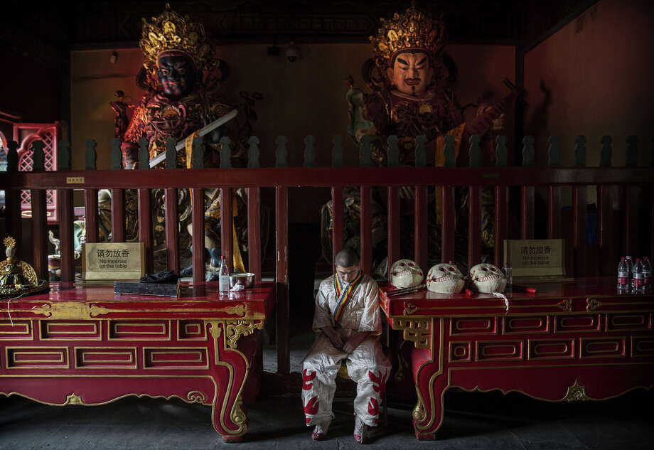 combo cap hereA Tibetan Buddhist monk waits inside a temple before taking part in the Beating Ghosts ritual at the Lama Temple, or Yonghegong on March 19, 2015 in Beijing, China. The ritual is held on the the 29th day of the first month after Losar, or New Year and is meant to expel evil spirits. (Photo by Kevin Frayer/Getty Images) Photo: Kevin Frayer / Getty Images / 2014 Getty Images