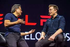 Elon Musk (right) predicts that human drivers will be banned as auto-pilot vehicles take over the roads.