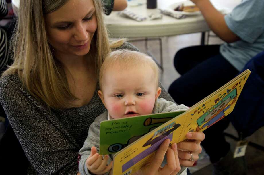 College- educated parents spend about 50 percent more time with young children on developmental activities like reading. Kids from poorer households spend that time in front of the TV. Photo: Andrew Whitaker /Associated Press / The Saginaw News | MLive.com