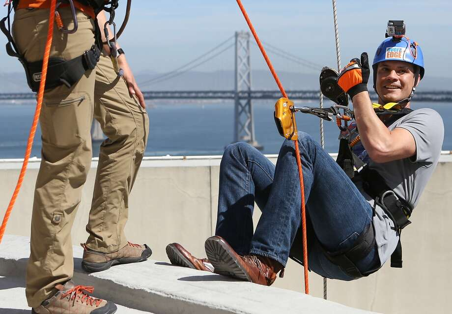 Grant Lotus begins his rappel down the 23 stories of  the Hyatt Regency in San Francisco on Thursday, March 19, 2015 in a fundraiser for non profits Over the Edge and Outward Bound. Photo: Amy Osborne, The Chronicle