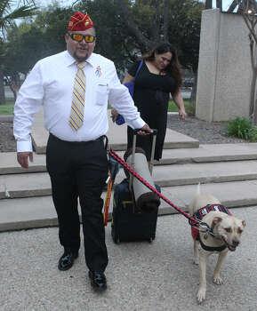 Juan Alonzo Miranda walks with his service dog, Goldie, to the courthouse Monday. Photo: John Davenport /San Antonio Express-News / ©San Antonio Express-News/John Davenport
