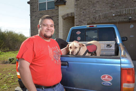 Juan Alonzo-Miranda is shown with his service dog, Goldie, in front of their far West Side home. Photo: Robin Jerstad /San Antonio Express-News