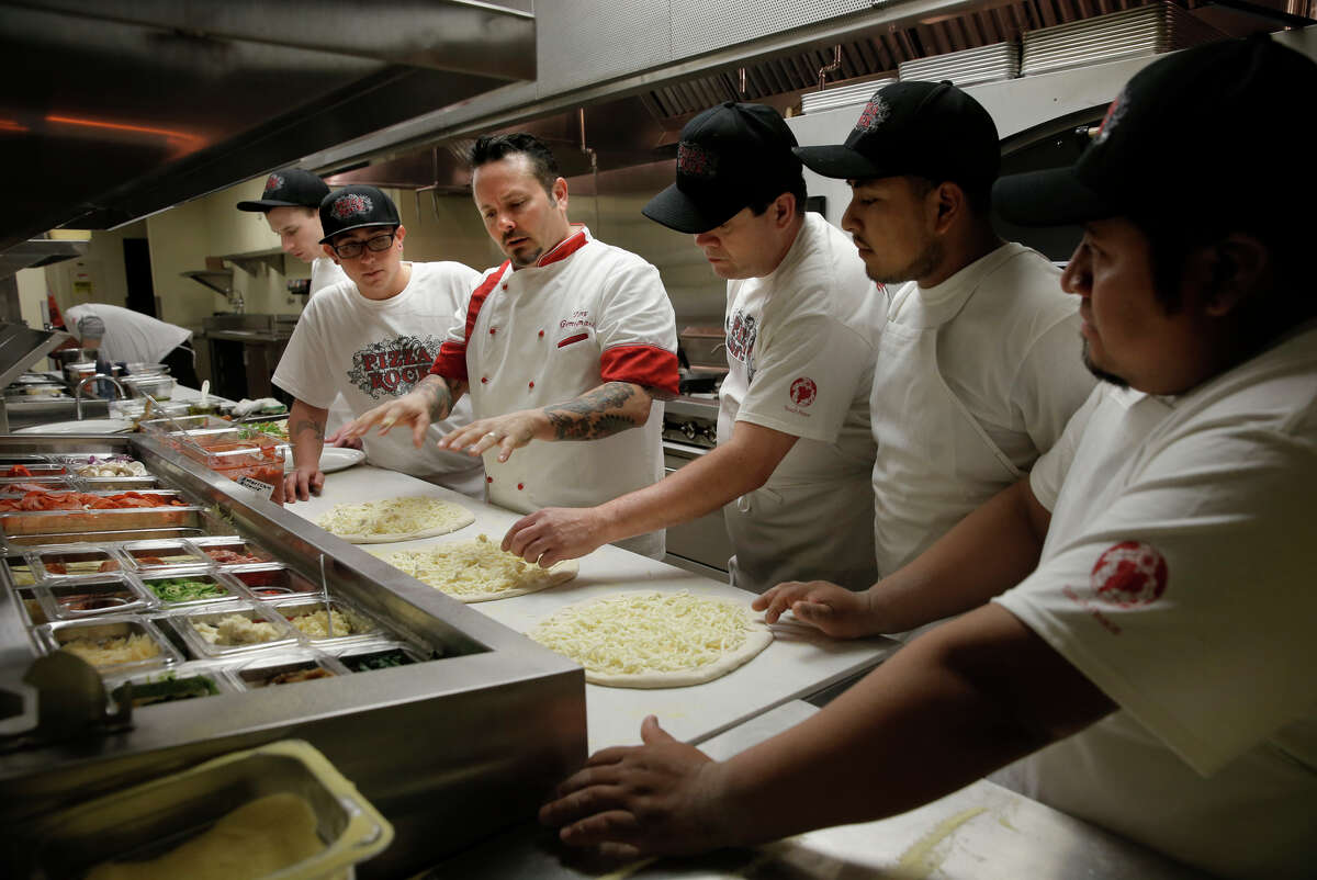 At Pizza Rock near Las Vegas, Tony Gemignani (center) demonstrates the proper technique to his kitchen staff.
