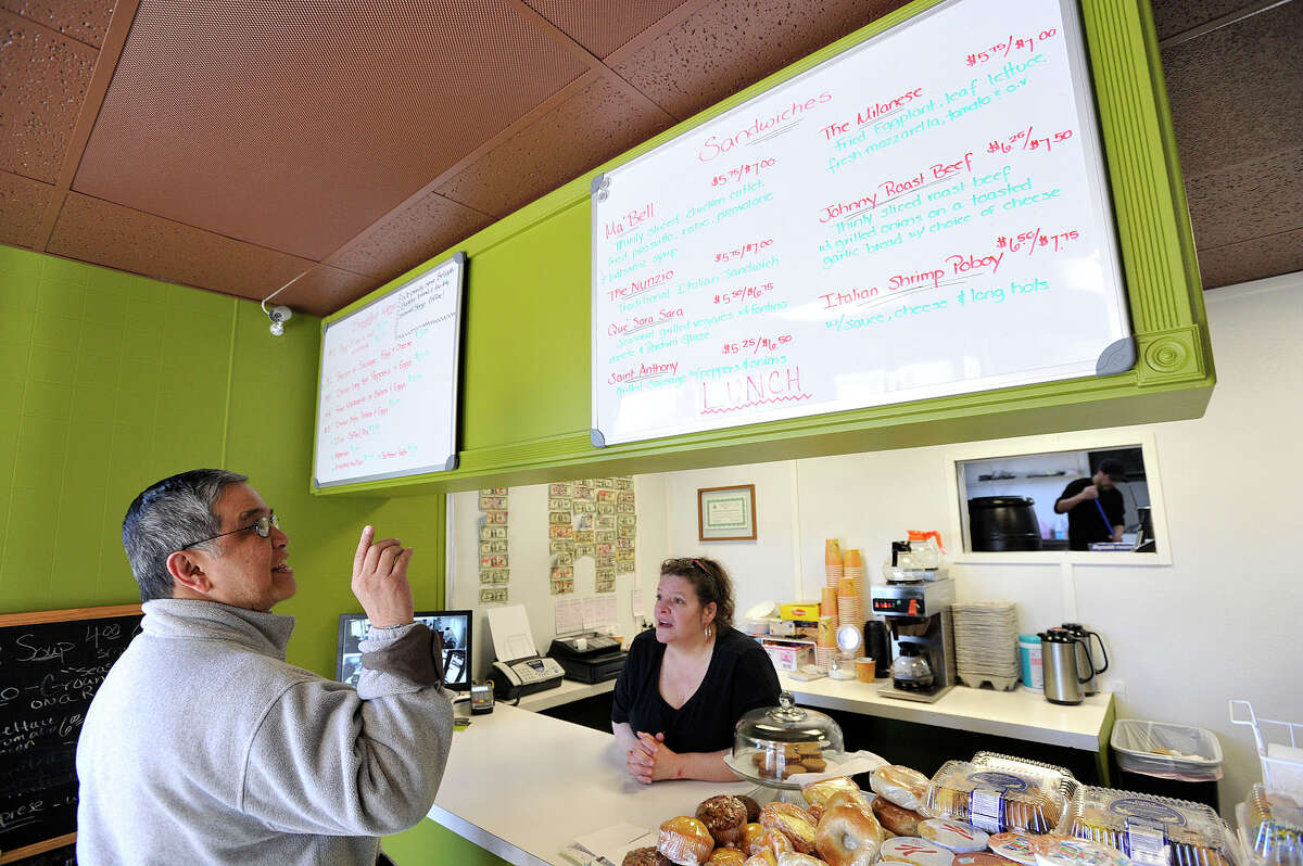 Napoleon Flores orders lunch to-go from Vita Grieco as Tony Collazo sweeps the floor in the kitchen, through the window at right, at Nunzio's Corner Kitchen in the Springdale neighborhood of Stamford, Conn., on Thursday, March 19, 2015. Flores' favorite sandwich is the Johnny Roast Beef. The restaurant recently opened its doors at Camp Avenue and Ryan Street.