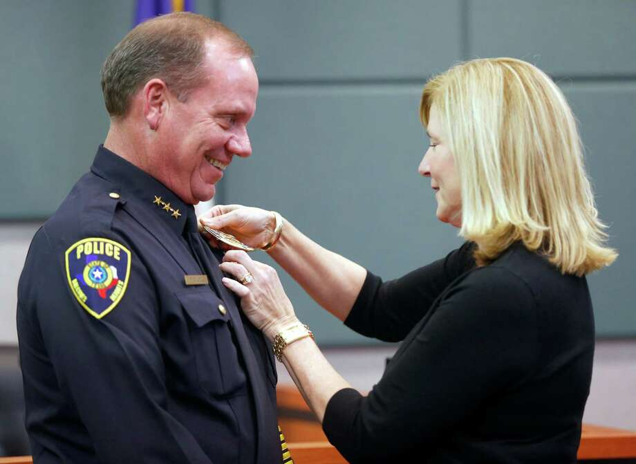 The newly-appointed Balcones Heights police chief Darrell Volz receives his badge Thursday afternoon March 19, 2015 from his wife, Diana, after he took the oath of office. Volz is a retired SAPD officer. Photo: William Luther, Staff / San Antonio Express-News / © 2015 San Antonio Express-News
